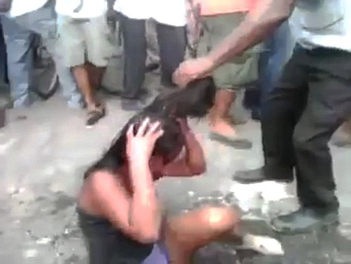 Pic shows: Moment the girl is bleeding from the face as the mob surround her. Horrific video of a vigilante mob burning a girl to death after beating her up has gone viral. The shocking 4-minute-38-second clip shows the 16-year-old girl bleeding from the face as the baying mob surround her in the village of Rio Bravo, 77 miles west of the Guatemala capital, Guatemala city. According to reports, the girl who has not been named but is said to have been a clothes seller, was set upon after allegedly murdering a taxi driver. Locals say the girl and two men shot driver Carlos Enrique González Noriega, 68, dead before robbing him and running off. The two men fled down a series of alleys, but the girl took a wrong turn and was surrounded by the fuming 250-strong mob. After viciously beating her, the video shows her stumbling around bleeding from the face. At one point she is punched to the ground and set upon again as the mob demand justice. She is then set on fire and filmed writing and screaming in pain as the lynch mob watch on. At one point she tries to run away but then collapses on the ground in flames. As she lies burning to death, a man runs over with a can of petrol and puts it over her sending her up in flames again. The girl screams out in pain and then passes out. The mob, which include children, continue to stand and watch as her lifeless body is consumed by flames and left as a smouldering corpse. A police spokesman said that officers had tried to intervene but were blocked by the vigilante mob. The video which was uploaded to YouTube has since been removed after being viewed hundreds of thousands of times within just hours. Police say they are now investigating the attack. (ends)